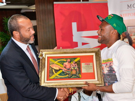 World Boxing Association super featherweight champion, Nicholas 'The Axeman' Walters (right), is presented with a plaque by deputy director of the Jamaica Tourist Board, Jason Hall, when he arrived at the Sangster International Airport in Montego Bay, yesterday