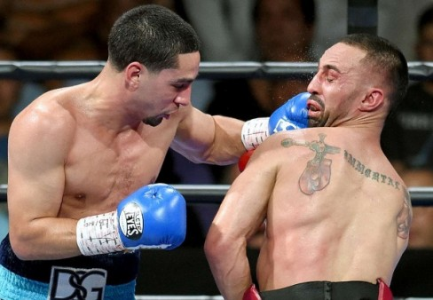 After being battered from pillar to post, the referee stepped in to save Malignaggi, both from Garcia and himself.  (Photo: Naoki Fukuda)